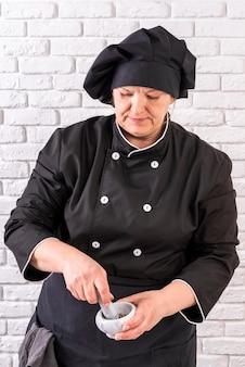 Vue frontale, de, femme, chef cuisinier, utilisation, mortier, et, pilon