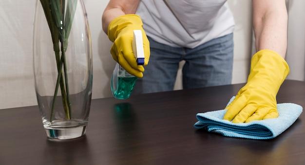 Vue frontale, de, femme, à, gants caoutchouc, nettoyage table