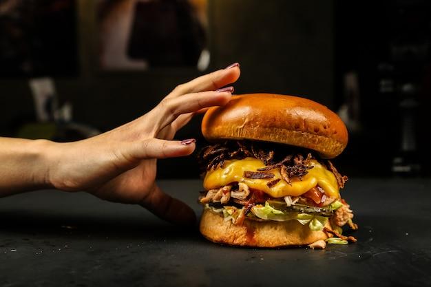 Vue frontale, femme, manger viande hamburger