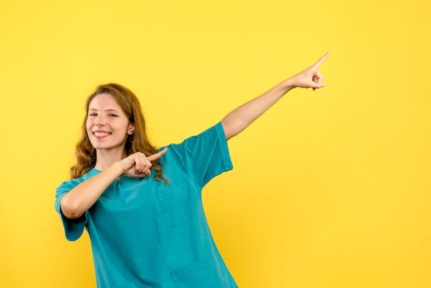 Vue frontale, de, femme médecin, sourire, sur, mur jaune