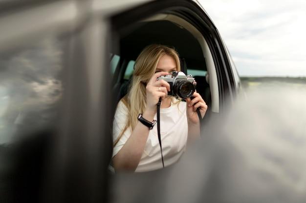 Vue frontale, de, femme, prendre photos, à, appareil photo, depuis, voiture