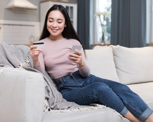 Vue frontale, de, femme, sur, sofa, commande en ligne, utilisation, carte de crédit