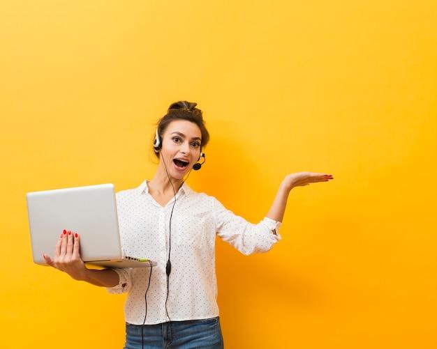 Vue frontale, de, femme souriante, porter, casque à écouteurs, et, tenue, ordinateur portable