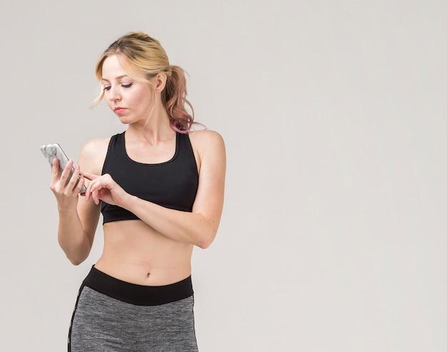 Vue frontale, de, femme sportive, regarder, elle, smartphone
