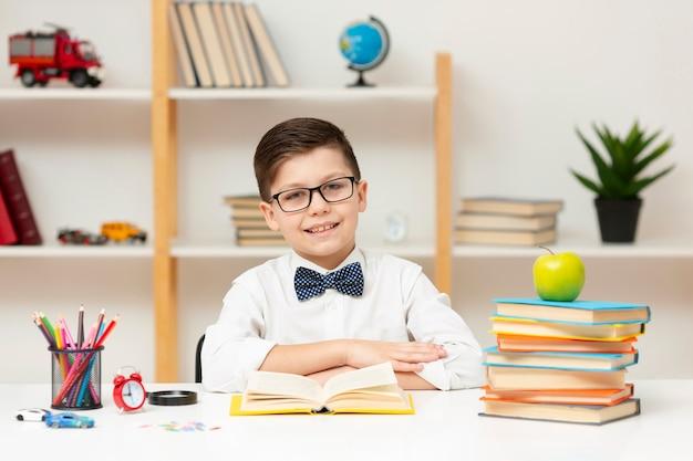 Vue frontale, garçon, bureau, lecture