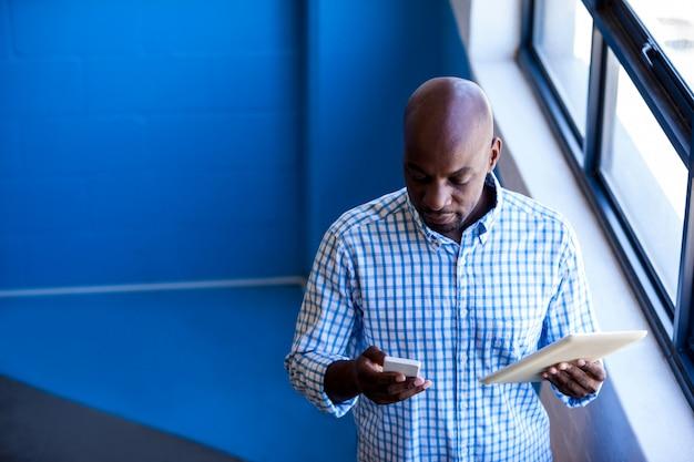 Vue frontale, de, homme affaires, debout, quoique, utilisation, tablette numérique