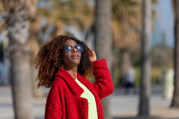 Vue frontale, de, jeune, belle, afro, bouclé, lunettes lunettes soleil, et, veste rouge, debout, dans, a, rue ville, tout, toucher cheveux, et, sourire, dans, une, journée ensoleillée