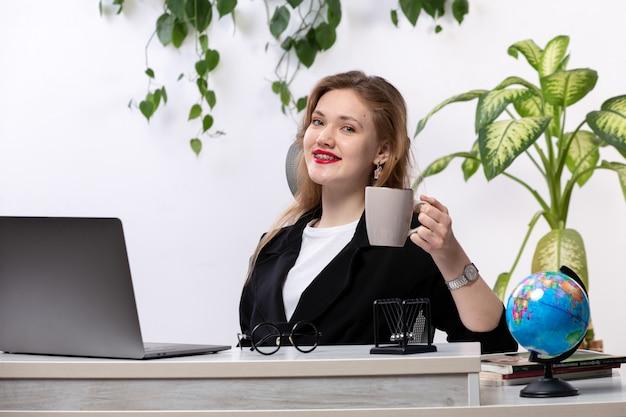 A, vue frontale, jeune, belle dame, dans, chemise blanche, et, veste noire, utilisation, elle, ordinateur portable, devant, table, sourire, tenue, tasse, à, feuilles, pendre