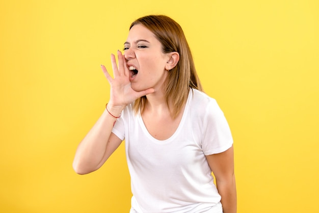 Vue frontale, de, jeune femme, appel, sur, mur jaune