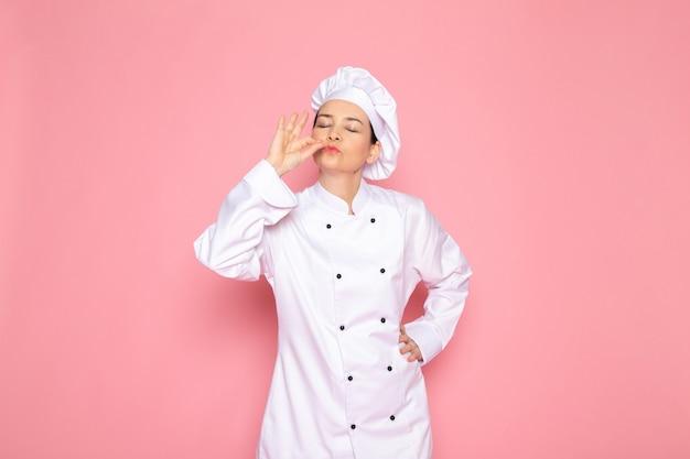 A, vue frontale, jeune femme, cuisinier, dans, cuisinier blanc, complet, blanc, casquette, sourire, poser, délicieux, signe, heureux
