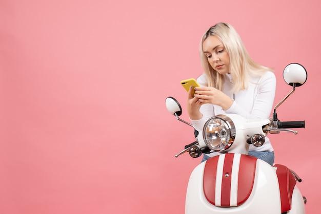 Vue frontale, jeune femme, sur, cyclomoteur, regarder, téléphone