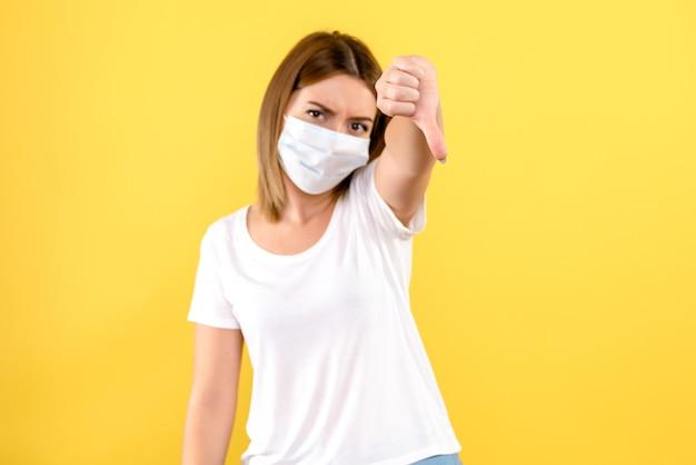 Vue frontale, de, jeune femme, dans, masque, sur, mur jaune