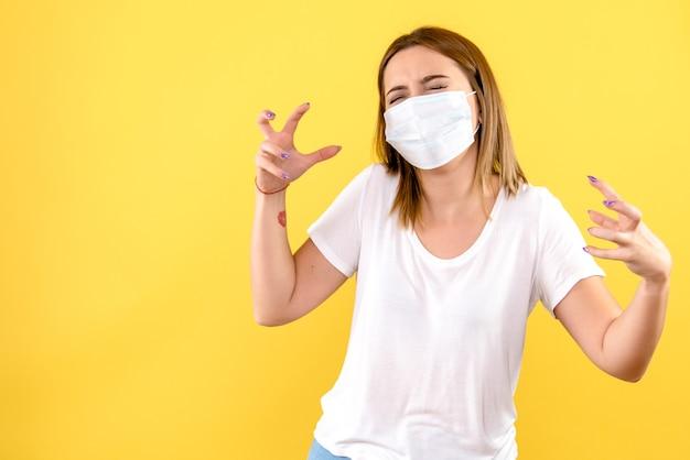 Vue frontale, de, jeune femme, dans, masque stérile, sur, mur jaune