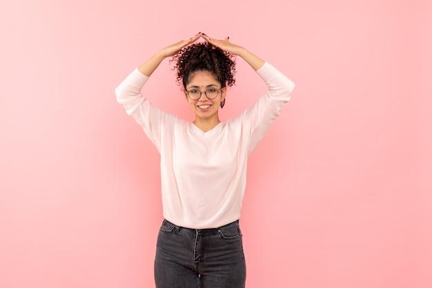 Vue frontale, de, jeune femme, sourire, sur, mur rose
