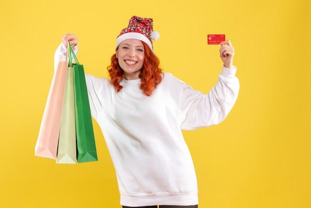 Vue frontale, de, jeune femme, tenue, achats, paquets, et, carte bancaire, sur, mur jaune