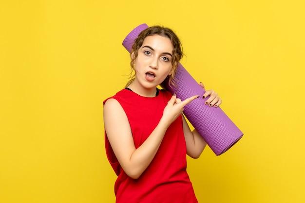 Vue frontale, de, jeune femme, tenue, tapis violet, sur, mur jaune clair
