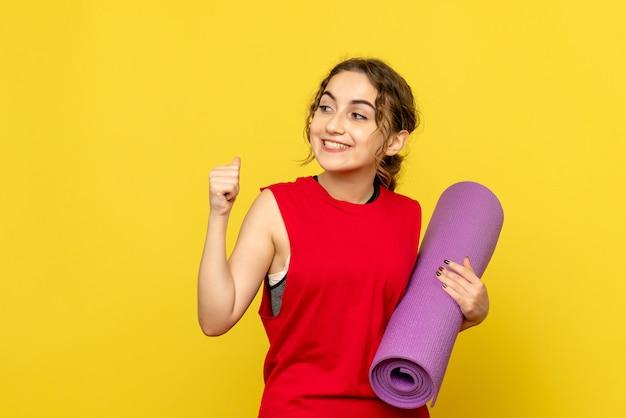 Vue frontale, de, jeune femme, tenue, tapis violet, sur, mur jaune