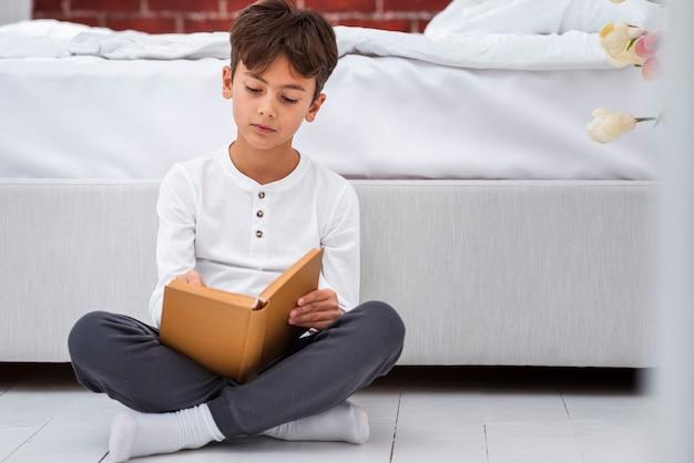 Vue frontale, jeune garçon, chez soi, lecture
