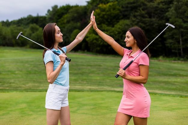 Vue frontale, de, jeune, golfeurs, haut fiving