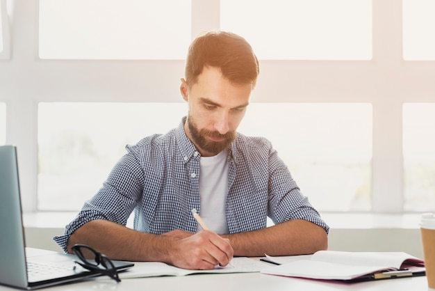 Vue frontale, jeune homme, bureau, écriture