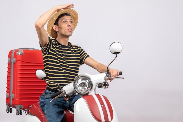 Vue frontale, de, jeune homme, à, chapeau paille, sur, cyclomoteur, regarder quelque chose