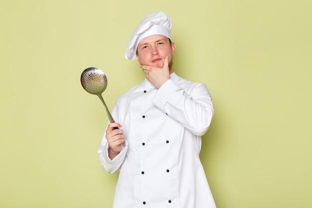 A, vue frontale, jeune, mâle, cuisinier, dans, blanc, cuisinier, complet, tête blanche, chapeau, tenue, grand, argent, cuillère, pensée