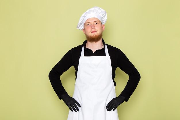 A, vue frontale, jeune, mâle, cuisinier, dans, chemise noire, à, cape blanche, tête blanche, chapeau, dans, gants noirs, poser