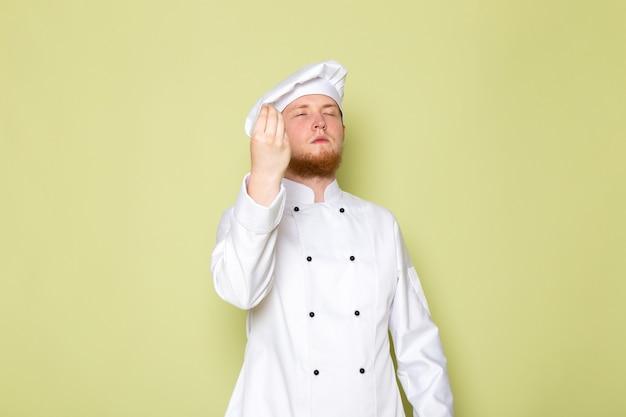 A, vue frontale, jeune, mâle, cuisinier, dans, cuisinier blanc, complet, casquette tête blanche, savoureux, signe