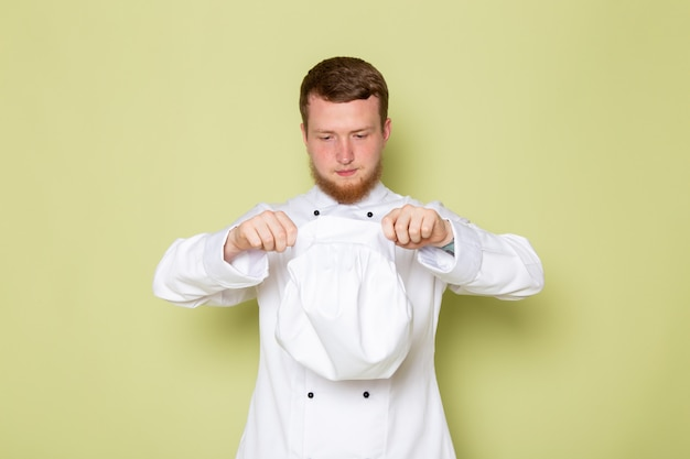 A, vue frontale, jeune, mâle, cuisinier, dans, cuisinier blanc, complet, enlever, sien, casquette blanche