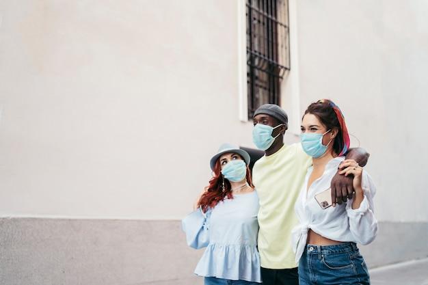Vue frontale de joyeux amis interraciaux avec masque chirurgical bleu. ils marchent le long de la ville. homme africain soutenu sur les femmes rousses et brunes.