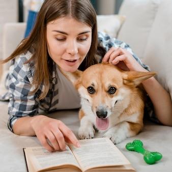 Vue frontale, de, lecture livre femme, à, chien, sur, divan