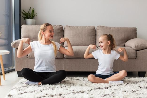 Vue frontale, de, mère fille, chez soi, montrer biceps