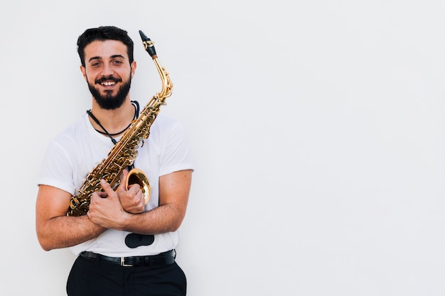 Vue frontale moyen coup musicien souriant avec saxophone