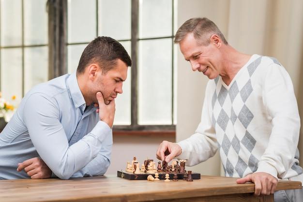 Vue frontale, de, père fils, jouer échecs