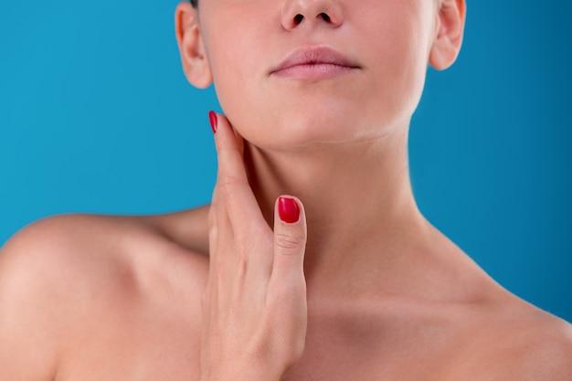 Vue frontale recadrée du modèle touchant son visage et son cou avec tendresse. mains féminines avec des ongles précis sur studio bleu. lisse ton peau saine