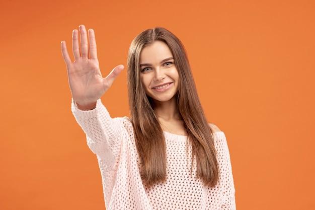 Vue frontale, de, smiley, femme, mettre, elle, main, haut, comme, arrêt