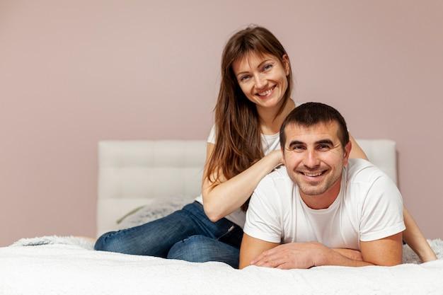 Vue frontale, sourire, couple, séance lit