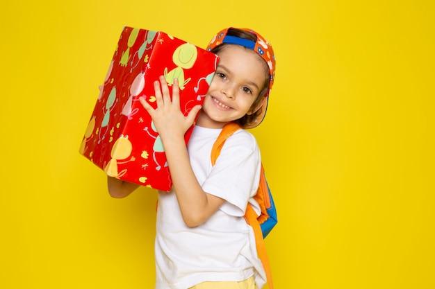 Vue frontale, sourire, garçon, tenue, rouges, conçu, présent, dans, t-shirt blanc, sur, bureau jaune