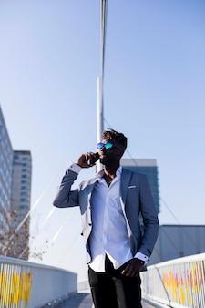 Vue frontale, de, sourire, jeune homme africain noir, porter, élégants, debout, dans, rue, tout, à l'aide de, téléphone portable, dehors, dans, ensoleillé