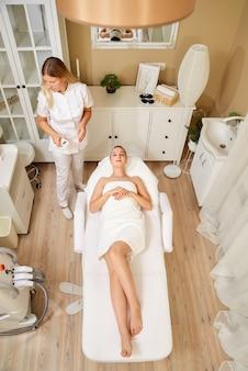 Vue générale du salon de beauté du spa. maître esthéticienne et cliente