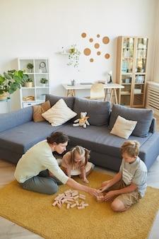 Vue grand angle à aimer la famille avec peu de besoins spéciaux fille jouant à des jeux de société alors qu'il était assis sur le sol à la maison, copiez l'espace