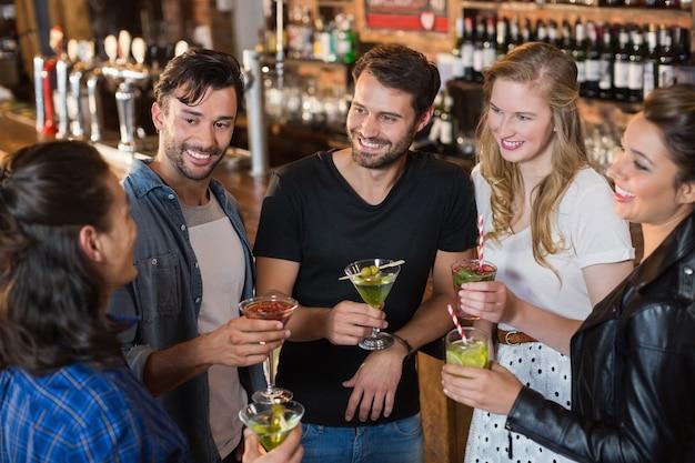 Vue grand angle d'amis souriants tenant des boissons tout en se tenant debout ensemble
