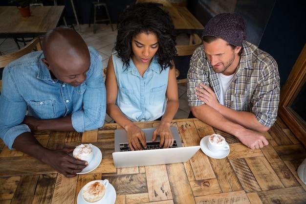 Vue grand angle d'amis utilisant un ordinateur portable à table en bois dans un café