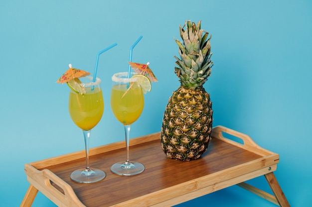 Vue grand angle de l'ananas et deux verres avec des cocktails d'été exotiques décorés avec un parapluie à cocktail sur plateau de service en bambou