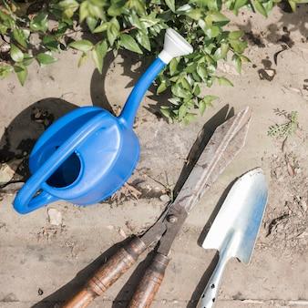 Vue grand angle de l'arrosoir; pelle à main et ciseaux de jardinage près de feuilles vertes