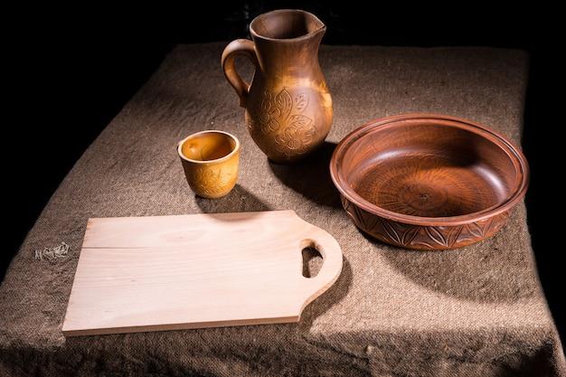Vue en grand angle de l'artisanat, d'un bol en bois sculpté, d'un pichet et d'une tasse et d'une planche à découper ordinaire sur une table recouverte de toile de jute
