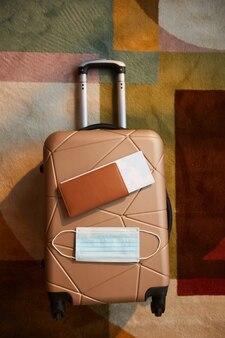 Vue grand angle des bagages avec des documents et un masque de protection dessus