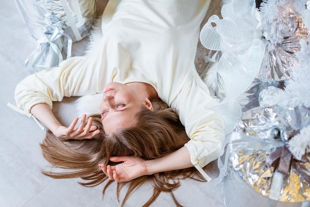Vue grand angle d'une belle femme caucasienne allongée sur le sol près d'un arbre de noël avec des cadeaux en haut...