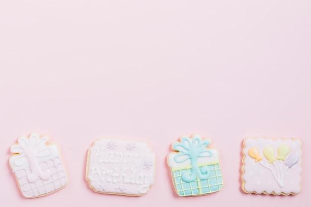 Vue grand angle de biscuits d'anniversaire sur fond rose