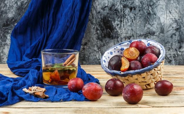 Vue grand angle boisson fermentée et cannelle sur foulard bleu avec un bol de prunes sur planche de bois et surface en marbre gris foncé. horizontal